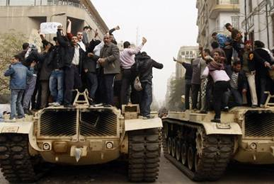 Protesters stand on Tanks and Chant Slogans for Change