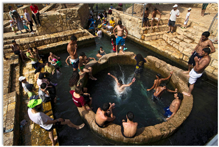 Israelis and Palestinians cool themselves off at the Ein Fuar spring located Jericho