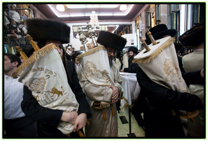 Ultra-Orthodox Jewish men carry Torah scrolls as they dance during Simchat Torah