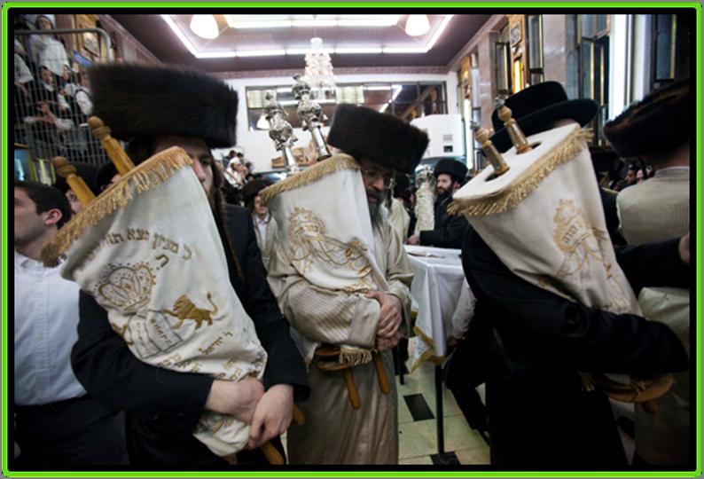 Ultra-Orthodox Jewish men carry Torah scrolls as they dance during Simchat Torah