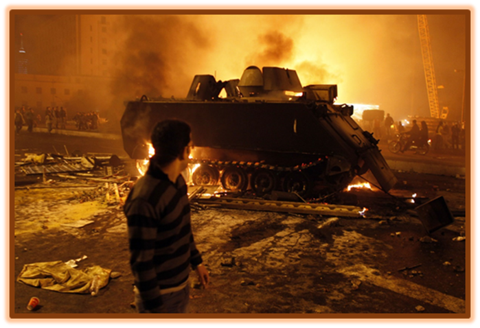 Protestor looking at a Burned Armored Vehicle in downtown Egypt