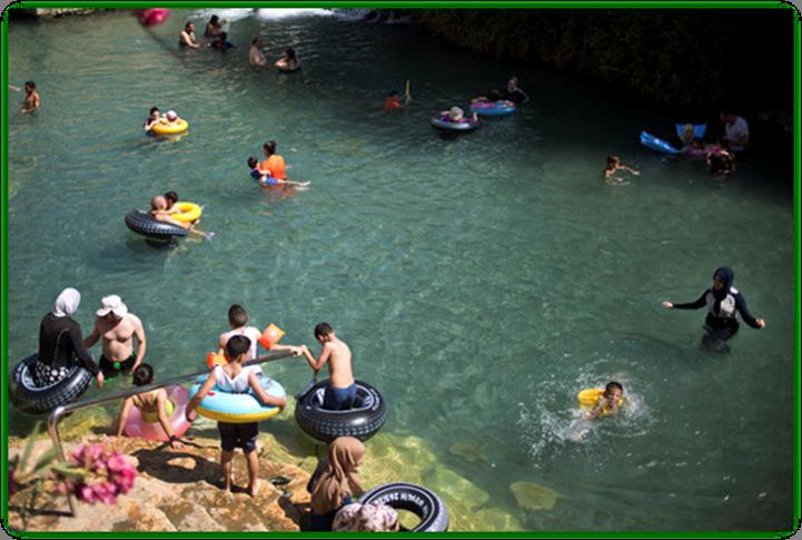 Jewish families cool off at the Gan HaShlosha National Park in Israel