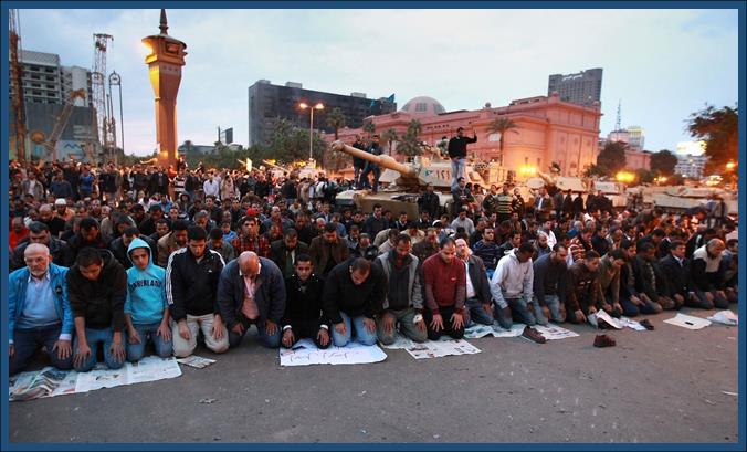 Egyptians praying in the Tahir Square in front of Army Tank
